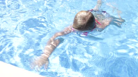 plavat : Young girl wearing goggles swims to edge of pool and waves at camera.