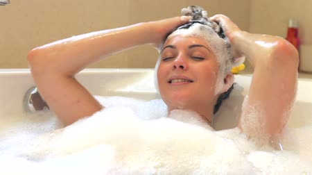banyo : Relaxed woman lying in bubble filled bath washing her hair.