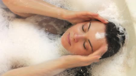 wanna : Relaxed woman lying in bubble filled bath washing her hair.