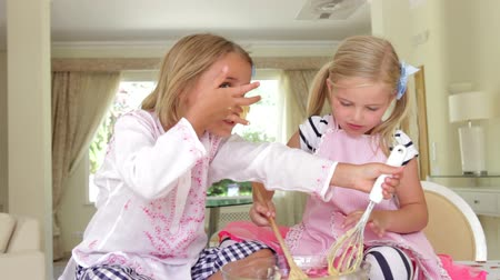 ложка : Two girls sitting at kitchen table tasting cake mixture from bowl before putting some on each others noses.