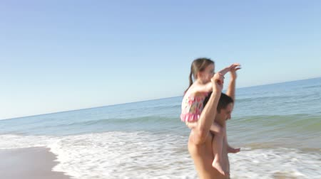 vacation : Father carrying daughter on shoulders running along beach. Stock Footage