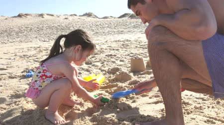 helping : Father helping daughter as she makes sandcastle.