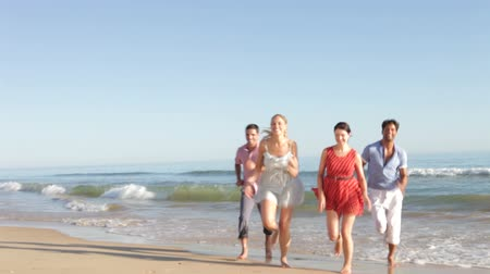 pan : Group of friends running up beach towards camera. Stock Footage
