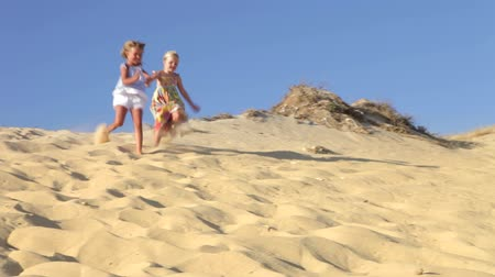 serpenyő : Two young girls running down sand dune past camera position.