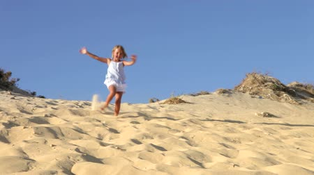 posição : Young girl running down sand dune past camera position.