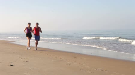 empty beach : Couple in sportswear running along empty beach towards and then past camera position.