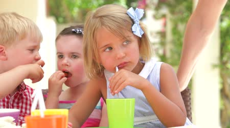 içme : Children sitting at table eating party food and talking with friends.