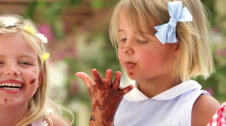 śmiech : Children sitting on table licking melted chocolate from fingers.
