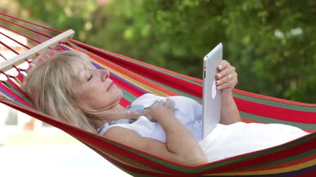 pihenő : Senior woman rocking in hammock using digital tablet.
