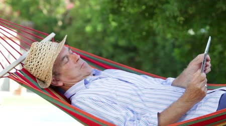 ogród : Senior man rocking in hammock using digital tablet.  Wideo