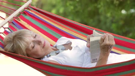 гамак : Senior woman rocking in hammock turning pages of book.