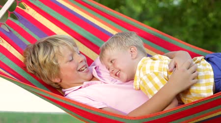 houpavý : Two boys relax together in hammock.