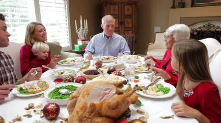 vacsora : Camera tracks across table as extended family sit and enjoy thanksgiving dinner.