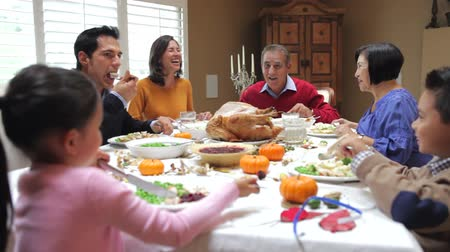Camera tracks across table as extended family sit and enjoy thanksgiving dinner.