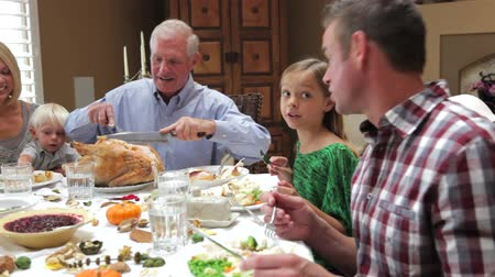 vacsora : Camera tracks across table as grandfather carves slices of turkey at thanksgiving dinner.