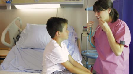 estetoscópio : Nurse greets boy sitting on bed before asking him to take breaths and listening through stethescope.  Vídeos