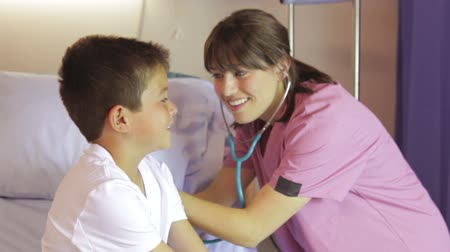 сотрудники : Nurse greets boy sitting on bed before asking him to take breaths and listening through stethescope.  Стоковые видеозаписи