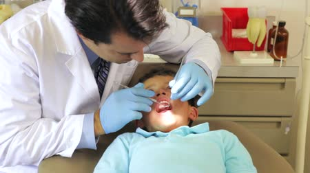 dişçi : Dentist examining teeth of young male patient.  Stok Video