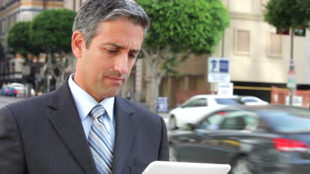 podnikatel : Businessman standing in street using a digital tablet.