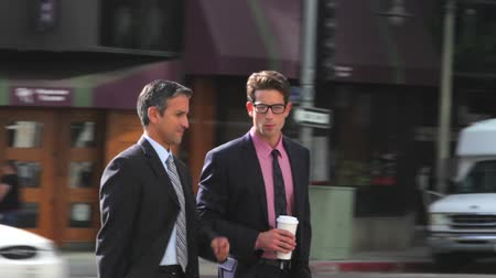xícara de café : Camera tracks two businessmen as they walk along street together chatting.