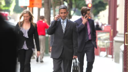 gotículas : Group of business people,some using mobile phones, walk into focus towards camera.