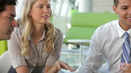 people talking : Camera tracks between businesspeople sitting and having an informal meeting looking at data on digital tablet together. Stock Footage