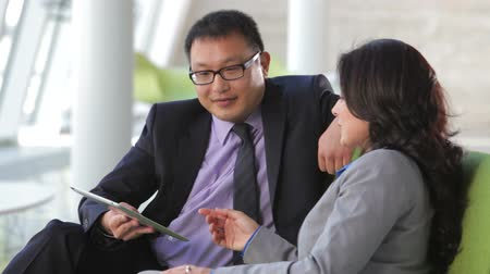 informal : Businesspeople sit and have informal meeting looking at data on digital tablet together. Stock Footage