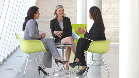 öltöny : Three businesswomen sit and have informal meeting discussing report together.