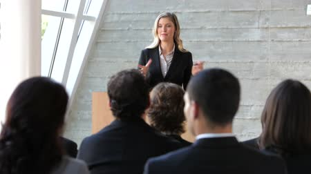 speaking : View from behind audience at business conference looking towards female speaker. Stock Footage