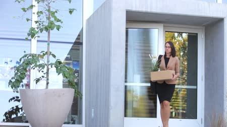 redundancy : Redundant businesswoman carrying box of personal possessions pushes open door of office and leaves.
