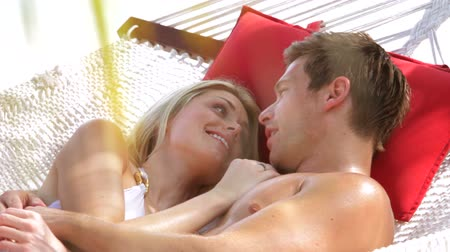 медовый месяц : Romantic Couple Relaxing In Beach Hammock Стоковые видеозаписи