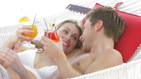 двадцатые годы : Romantic Couple Relaxing In Beach Hammock With Cocktails