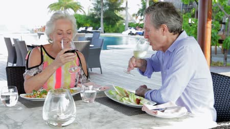 man eating : Senior Couple Enjoying Meal In Outdoor Restaurant
