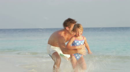 transportar : Father And Daughter Having Fun In Sea On Beach Holiday Stock Footage