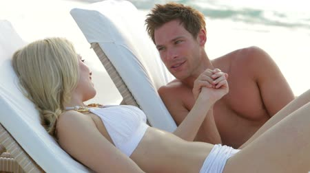 male : Romantic Couple Relaxing On Loungers At Beach  Stock Footage