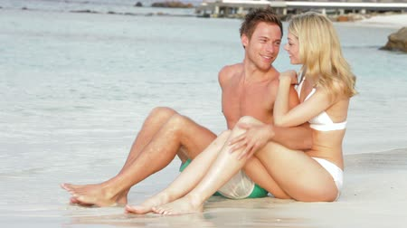 romantic couple : Romantic Couple Sitting By Shore At Beach