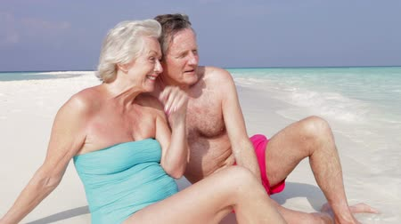 romane : Senior couple assis sur la belle plage