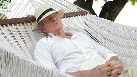 pihenő : Senior Man Relaxing In Beach Hammock  Stock mozgókép