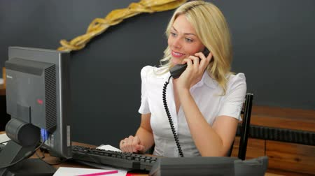 reception : Hotel Receptionist Using Computer And Phone Stock Footage