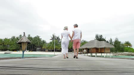atracação : Senior Couple Walking On Wooden Jetty