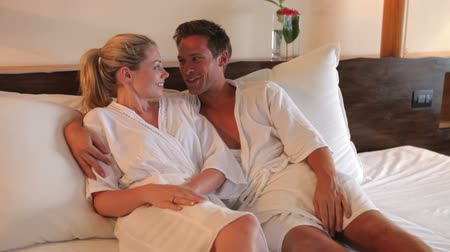 отель : Couple Relaxing In Hotel Room Wearing Robes