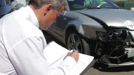 biztosítás : Loss Adjuster Inspecting Car Involved In Accident Stock mozgókép