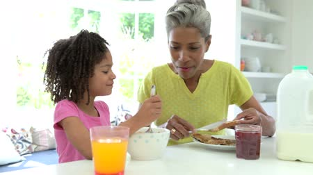 comer : Grandmother And Granddaughter Having Breakfast Together