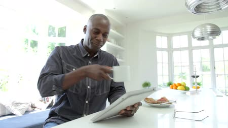 мужчины : African American Man Using Digital Tablet At Home