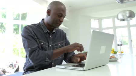 man eating : African American Man Using Laptop At Home