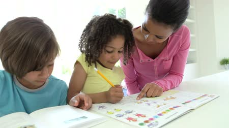 helping : Mother Helping Children With Homework Stock Footage