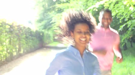 hareketli : Young African American Couple Running Along Country Path Stok Video