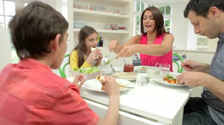 Hispanic Family Sitting At Table Eating Meal Together Stok Video