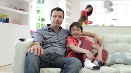 négy ember : Hispanic Family Sitting On Sofa Watching TV Together Stock mozgókép