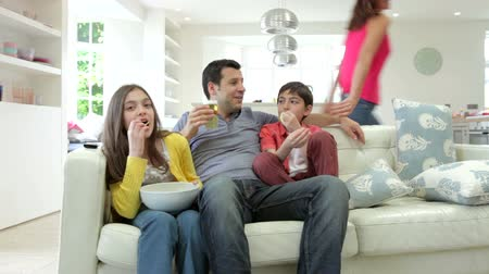 étkezik : Hispanic Family Sitting On Sofa Watching TV Together Stock mozgókép